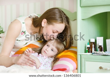 mother kisses the sick child - stock photo