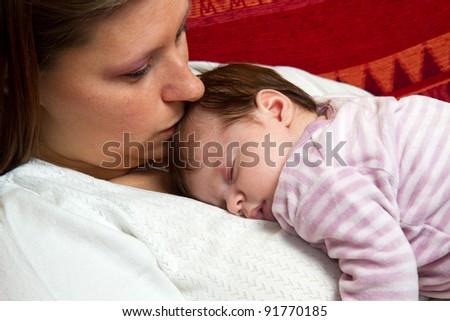 Mother kissing baby asleep - stock photo