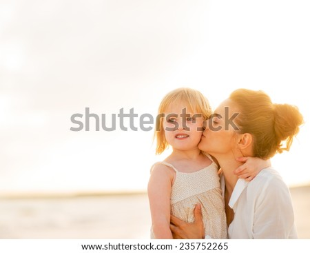 Mother kissing baby girl on beach at the evening - stock photo