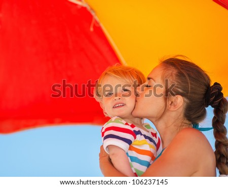 Mother kissing baby on beach under umbrella - stock photo