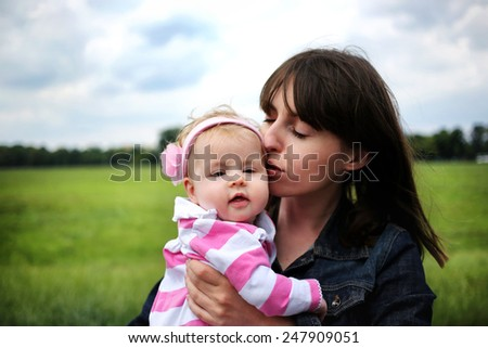 Mother kissing baby outdoors - stock photo
