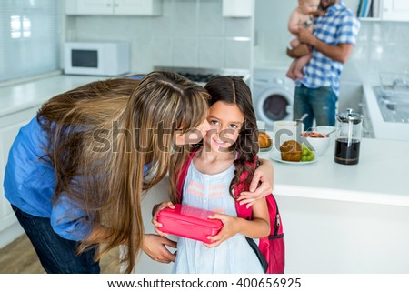 Mother kissing girl holding school lunch box with family in background at home - stock photo