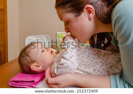 Mother kissing hands of her baby lying after the change of diaper - stock photo