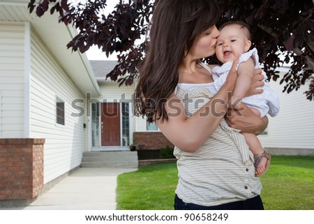 Mother kissing her adorable baby daughter - stock photo