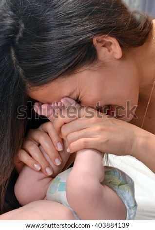 Mother kissing her baby feet. - stock photo