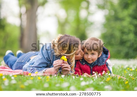 Mother kissing her cute little son while relaxing in nature  - stock photo