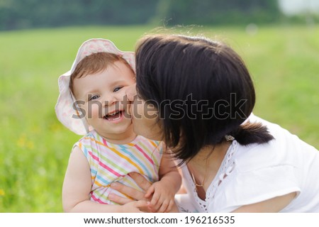 mother kissing her happy girl - stock photo