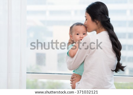 Mother kissing her little baby: family and motherhood - stock photo