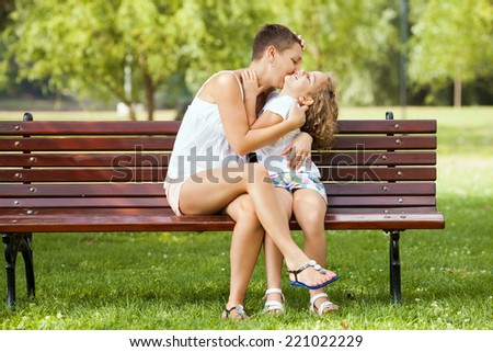 Mother kissing her little daughter in a park. - stock photo