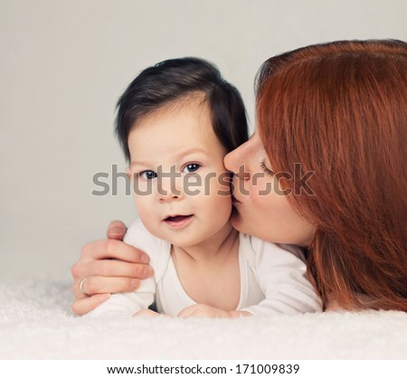 mother kissing her little newborn baby  - stock photo