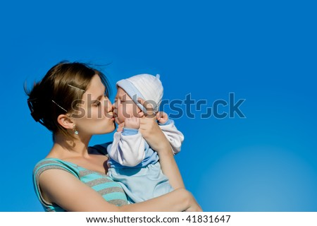 mother kissing her little son - stock photo