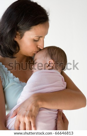 Mother kissing her sleeping baby - stock photo