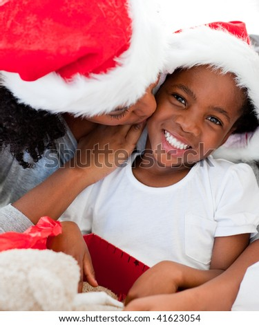 Mother kissing her smiling daughter at Christmas at home - stock photo