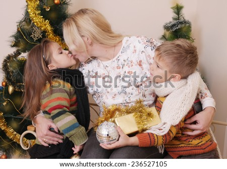 Mother kissing her two children over Christmas tree - stock photo