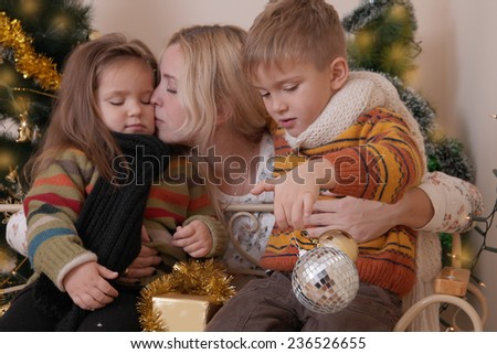 Mother kissing her two children under Christmas tree - stock photo