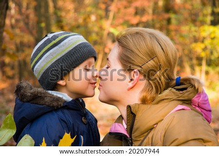 Mother kissing her 3 years old son in autumn scenery - stock photo