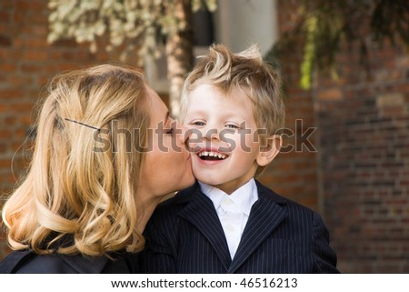 Mother kissing her 4 years old son outdoors - stock photo
