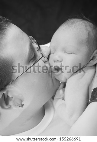 Mother kissing newborn baby - stock photo