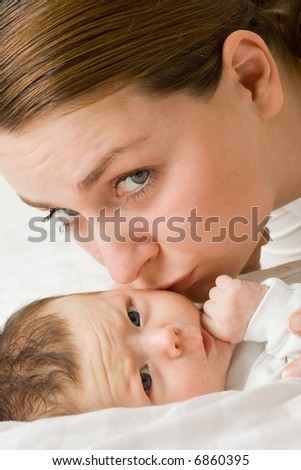 Mother kissing newborn baby on cheek - stock photo