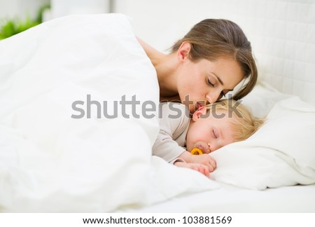 Mother kissing sleeping baby - stock photo