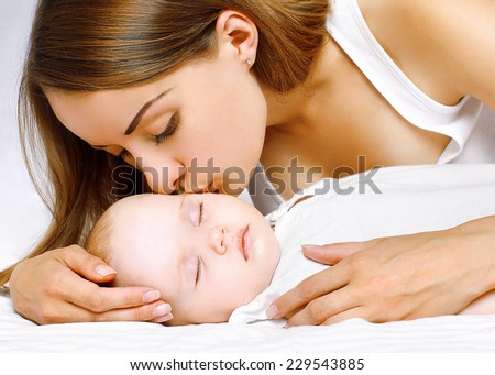 Mother kissing sleeping baby in bed home - stock photo