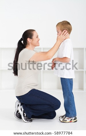 Mother kneeling down and comforting son against white background - stock photo