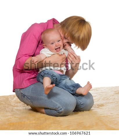 Mother kneeling on the floor with her laughing adorable baby cradled on her knees enjoyinga moment of joyful intimacy - stock photo