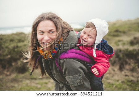 Mother laughing and having fun with your toddler outdoors