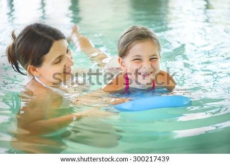 Mother learning to swim her little daughter in an indoor swimming pool. Having fun together. Kids swimming concept. - stock photo