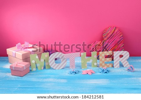 Mother- lettering of handmade paper letters on pink background - stock photo