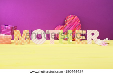 Mother- lettering of handmade paper letters on purple background - stock photo