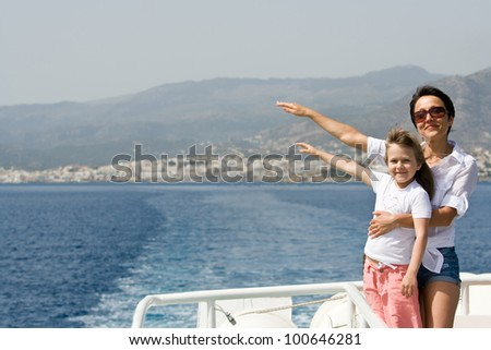 Mother, little child enjoy fresh summer wind and mountain seascape sailing by sea boat - stock photo