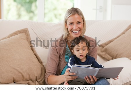 Mother looking at a book with her son at home - stock photo