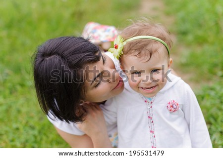 mother looking at her smiling daughter - stock photo