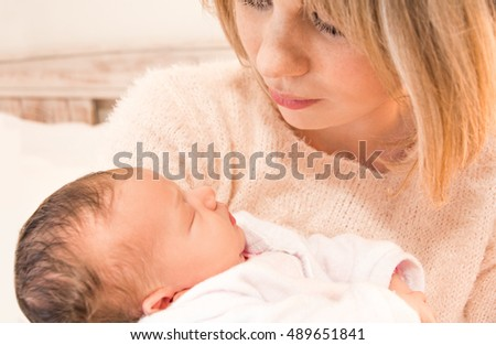 Mother looking down at her newborn baby girl in her arms