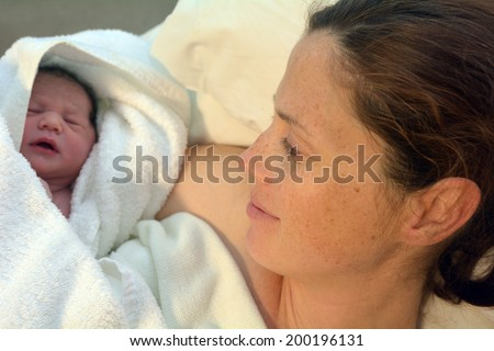 Mother looks at her newborn baby in bed immediately after a natural water birth labour. Concept photo of  pregnant woman, newborn, baby, pregnancy. - stock photo