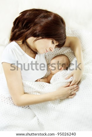 Mother lying down and embracing sleeping newborn baby. Protection and mother's love concept.