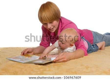 Mother lying on the floor with her arm protectively around her cute young baby looking at a book together - stock photo