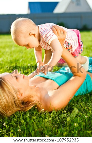 mother lying on the grass and holding baby in hands outdoors in sunlight in countryside - stock photo