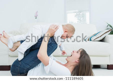 Mother lying playing with a baby in living room - stock photo