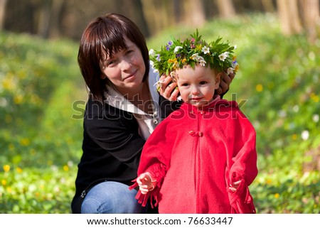 mother made ??a wreath of flowers for her daughter in the spring forest - stock photo