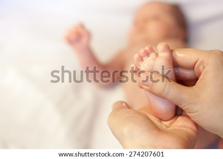 Mother makes massage for happy baby, apply oil on the foot, with white background with large space for any text
