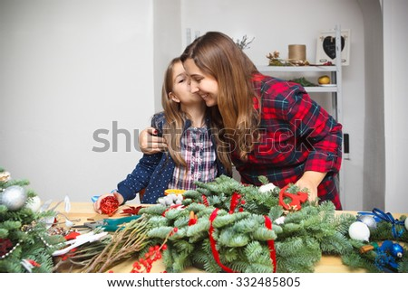 Mother making an advent wreath with daughter - dressed for the christmas - stock photo