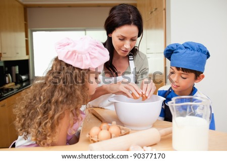 Mother making cookies together with her kids - stock photo