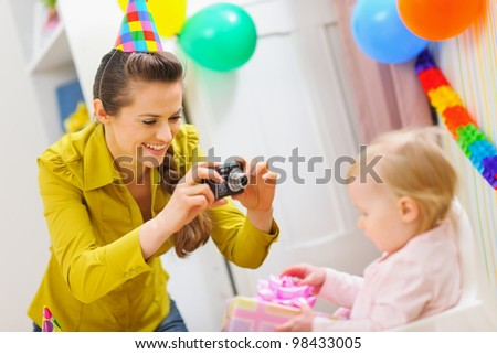 Mother making photos at babies birthday party - stock photo