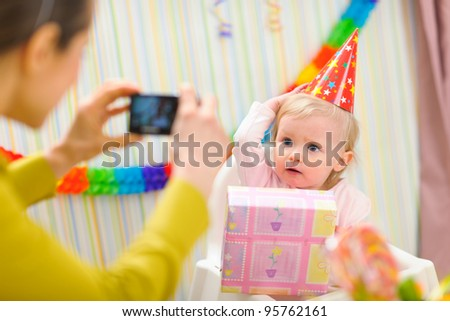 Mother making photos of babies first birthday - stock photo
