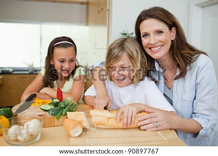Mother making sandwiches together with her children - stock photo