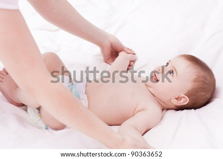 Mother massaging and exercise her little baby - stock photo