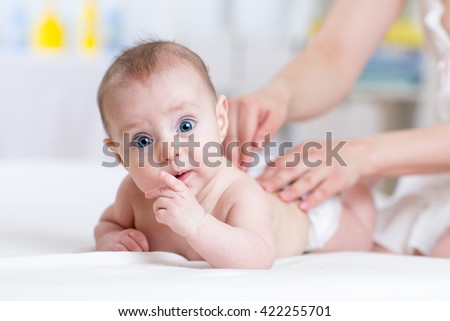Mother massaging baby infant in bed at home - stock photo