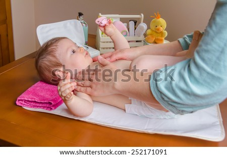 Mother massaging body of adorable baby lying after the change of diaper - stock photo
